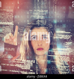 Serious female hacker using digital screen against abstract black room - Stock Photo