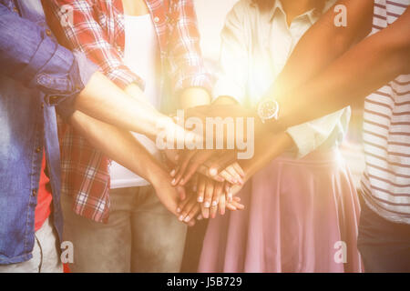Midsection of college students stacking hands while standing in classroom - Stock Photo