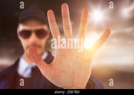 Confident security officer making stop gesture against open road - Stock Photo