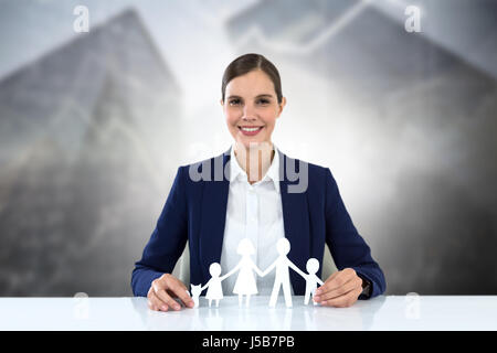 family in white paper with a woman in the background against digital composite of modern buildings - Stock Photo