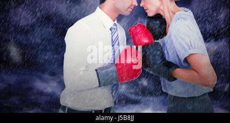 Business people wearing and boxing red gloves against gloomy sky - Stock Photo