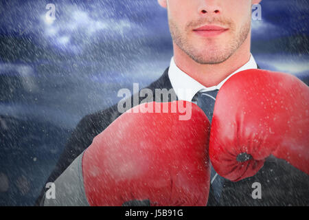 Businessman with boxing gloves against lightning strikes on landscape - Stock Photo