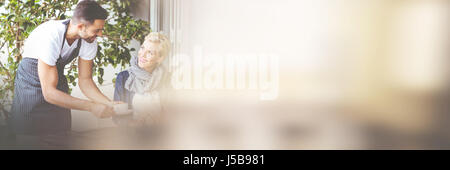 Waiter serving coffee to female customer at cafe - Stock Photo