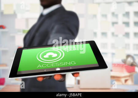 Midsection of businessman holding digital tablet against uploading symbol with text on green screen - Stock Photo