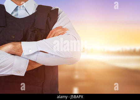Mid section of security officer standing with arms crossed against city on the horizon - Stock Photo