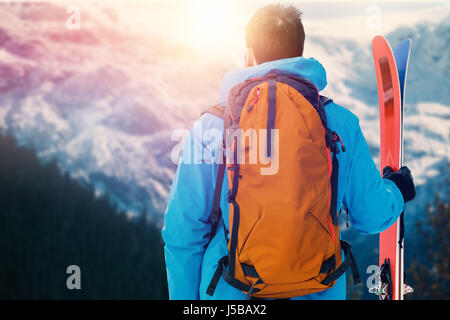 Rear view of skier with backpack holding skis against scenic view of forest and snowy mountain range - Stock Photo