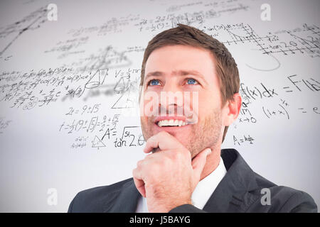 Businessman smiling and thinking against grey background - Stock Photo