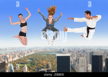 Man and women jumping over white background against new york - Stock Photo