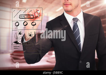 Businessman writing with a marker against digital image of workplace - Stock Photo