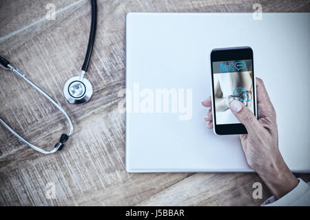 Fit woman with elbow injury against doctor using smartphone on wooden desk - Stock Photo