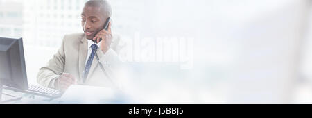 Smiling entrepreneur making phone call while looking at computer in office - Stock Photo
