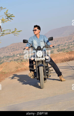 Young man on bike near mountain, Pune, Maharashtra - Stock Photo