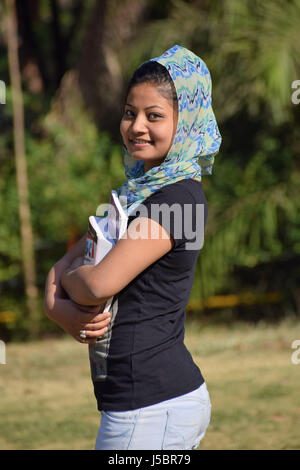 Beautiful young girl-student holding textbooks outside in the garden, Pune, Maharashtra - Stock Photo