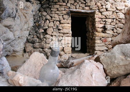 brown brownish brunette cave alcohol rock bottle dirty fusty stones steinhtte - Stock Photo