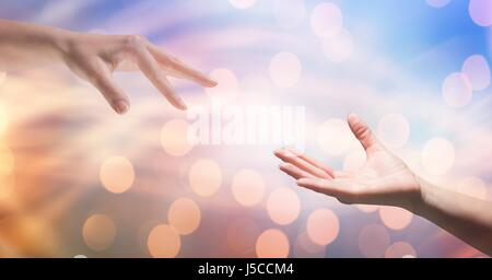 Digital composite of Cropped image of woman reaching man against bokeh - Stock Photo