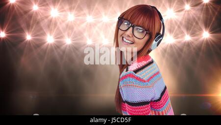 Digital composite of Redhead woman wearing headset against lights - Stock Photo