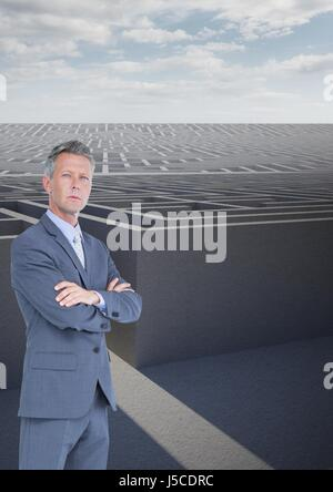 Digital composite of Businessman with arms crossed against maze - Stock Photo