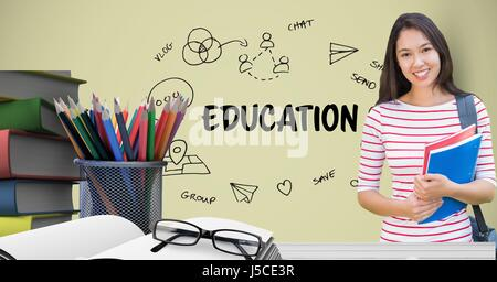 Digital composite of Female student holding books at table against education graphics - Stock Photo