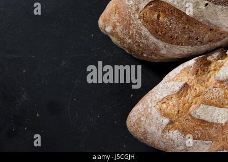 Rustic bread loaf on Black Slate Board. - Stock Photo