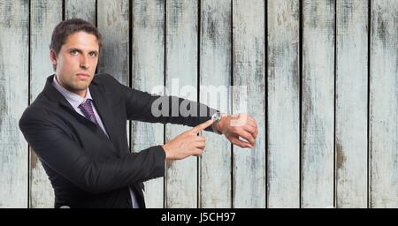 Digital composite of Portrait of angry businessman showing time on wristwatch against wooden wall - Stock Photo