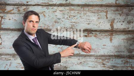 Digital composite of Portrait of businessman showing time on wristwatch against wooden wall - Stock Photo