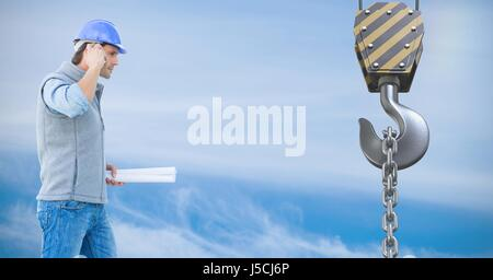 Digital composite of Architect using mobile phone in front of crane hook - Stock Photo