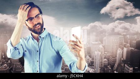 Digital composite of Hipster taking selfie though smart phone against city - Stock Photo