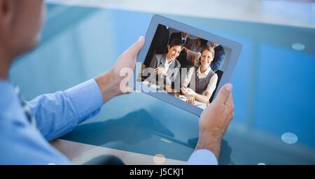 Digital composite of Businessman video conferencing on tablet PC - Stock Photo