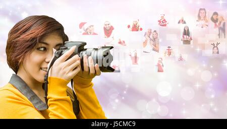 Digital composite of Female photographer using SLR camera by flying Christmas portraits - Stock Photo