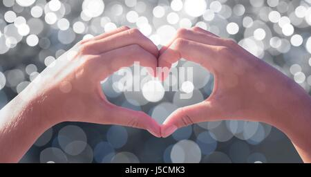 Digital composite of Cropped image of couple making heart shape with hands over bokeh - Stock Photo