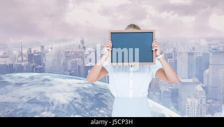 Digital composite of Businesswoman holding slate in front of face against globe and city - Stock Photo