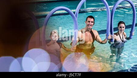 Digital composite of Smiling man and women with inflatable sticks in pool - Stock Photo