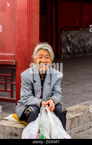 BEIJING, CHINA-26th MARCH 2014:-The old lady is resting beside a red wall outside the forbidden city - Stock Photo