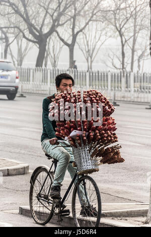 BEIJING, CHINA-26th MARCH 2014:-Street vendor with sugar coated syrup strawberries for sale - Stock Photo