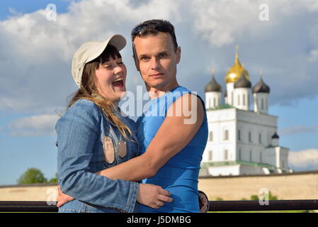 A young man embraces the girl on the background of the Trinity Cathedral in Pskov - Stock Photo