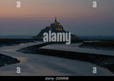 Mont Saint Michel sunset after dark Couesnon river scenic landscape seascape abbey atmospheric gloomy winding river - Stock Photo