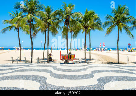 Bright scenic view of Copacabana Beach with palm trees beside the iconic boardwalk in Rio de Janeiro, Brazil - Stock Photo