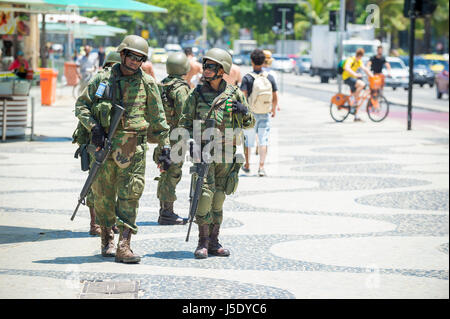 RIO DE JANEIRO - FEBRUARY 15, 2017: Brazilian Army soldiers patrol the boardwalk at Copacabana Beach to provide - Stock Photo