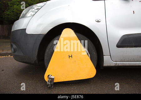 Impounded vehicle parked on street with vehicle immobiliser fitted (wheel clamp) by local authority, Merton, Southwest - Stock Photo