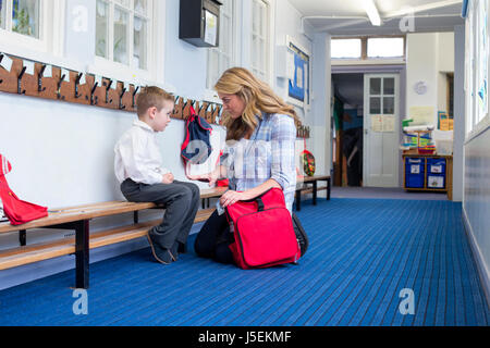 Young mother scolding her son in the corridor for bad behaviour in nursery. - Stock Photo