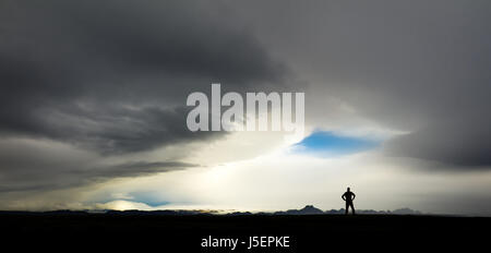 Silhouette of man watching huge storm and clouds in Iceland - Stock Photo
