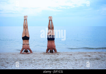 Svelte mature woman and strong man standing on head near sea - Stock Photo