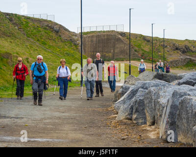 A group of senior people walking on the long-distance Cleveland Way in Skinningrove North Yorkshire - Stock Photo