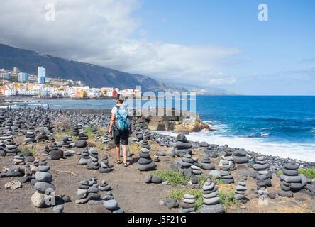 Puerto de La Cruz, Tenerife, Canary Islands, Spain. Female hiker on coastal footpath through stacks of balanced - Stock Photo