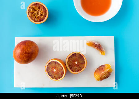 Whole, halved and squeezed blood oranges and fresh juice on white marble chopping board and solid blue background. - Stock Photo