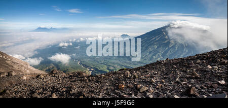 Sweeping panorama of the volcanic landscape viewed from Mount Merapi (Gunung Merapi) a high altitude volcano with - Stock Photo