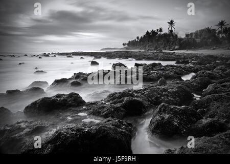 Beautiful black and white fine art picture of a Bali beach scene. Dramatic long exposure technique using monochrome - Stock Photo