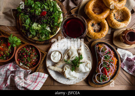 A lot of food on the wooden table. Georgian cuisine. Top view. Flat lay . Khinkali and Georgian dishes. - Stock Photo