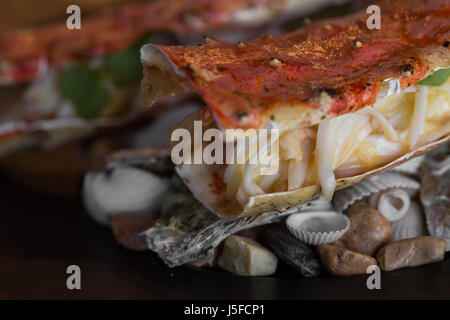 Dish of snow crab legs on the black plate. Selective focus. - Stock Photo