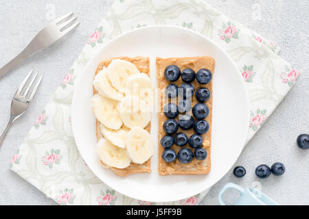 Healthy vegan peanut butter toasts with blueberries and banana slices on white plate. Top view - Stock Photo